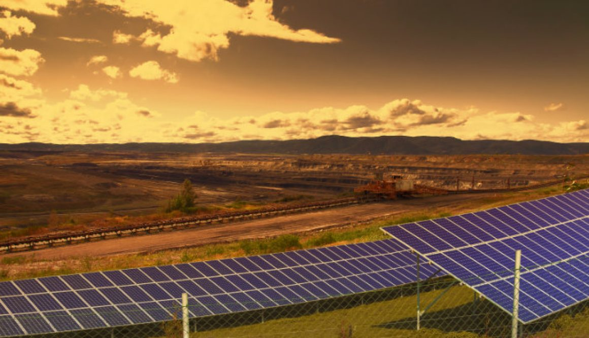 Coal mine with solar energy panels at sunset