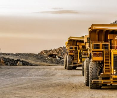 Large mining rock dump trucks transporting Platinum ore for processing